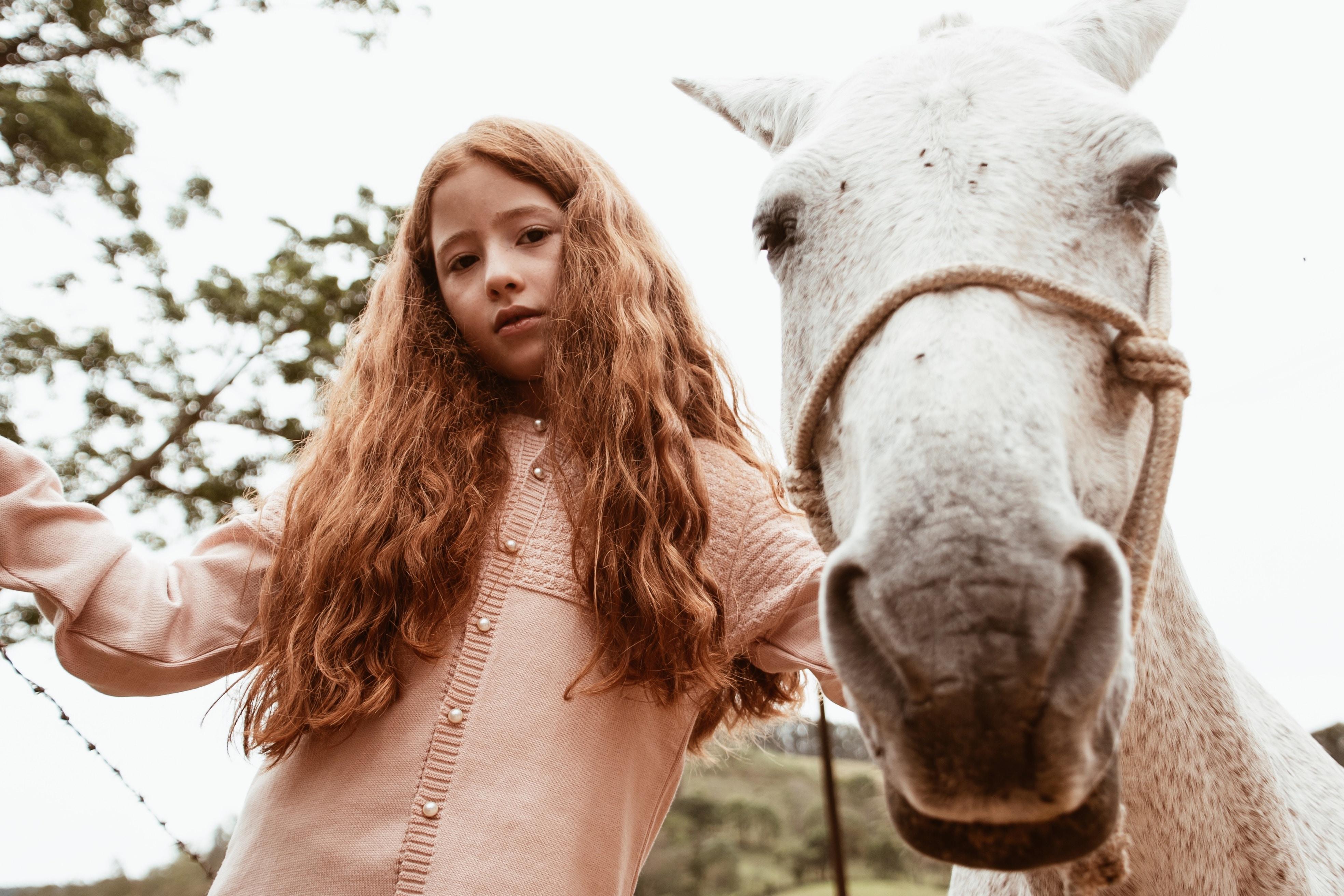 girl standing beside white horse