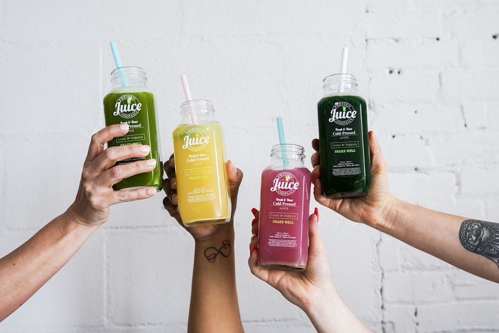 four hands holding juice bottles