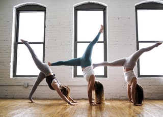 three woman doing hand stands