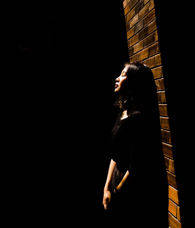 woman lying on brick wall