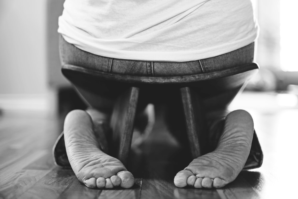 grayscale photography of person sitting on stool