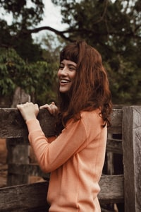 woman smiling hugging fence outdoor