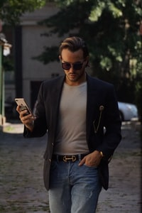 man in black suit jacket holding iPhone X