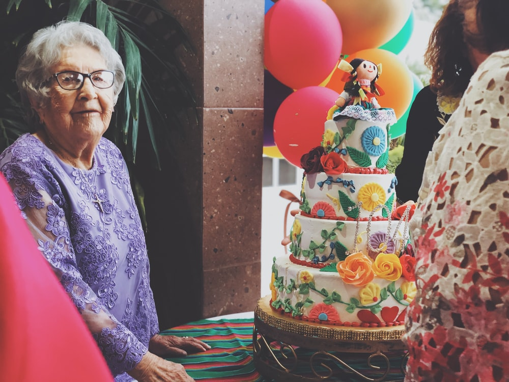 woman wearing purple floral long-sleeved dress besides 4-layer cake