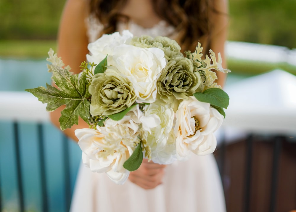 woman wearing white bridal gown holding white and green flower bouquet