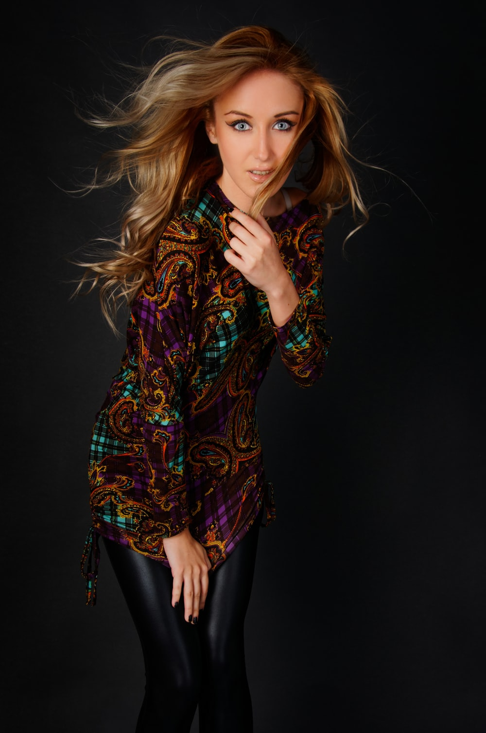 woman wearing multicolored long-sleeved top holding hair