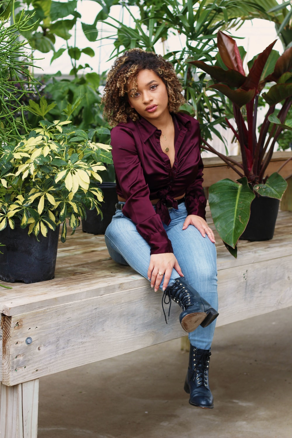 woman sitting beside plants on table