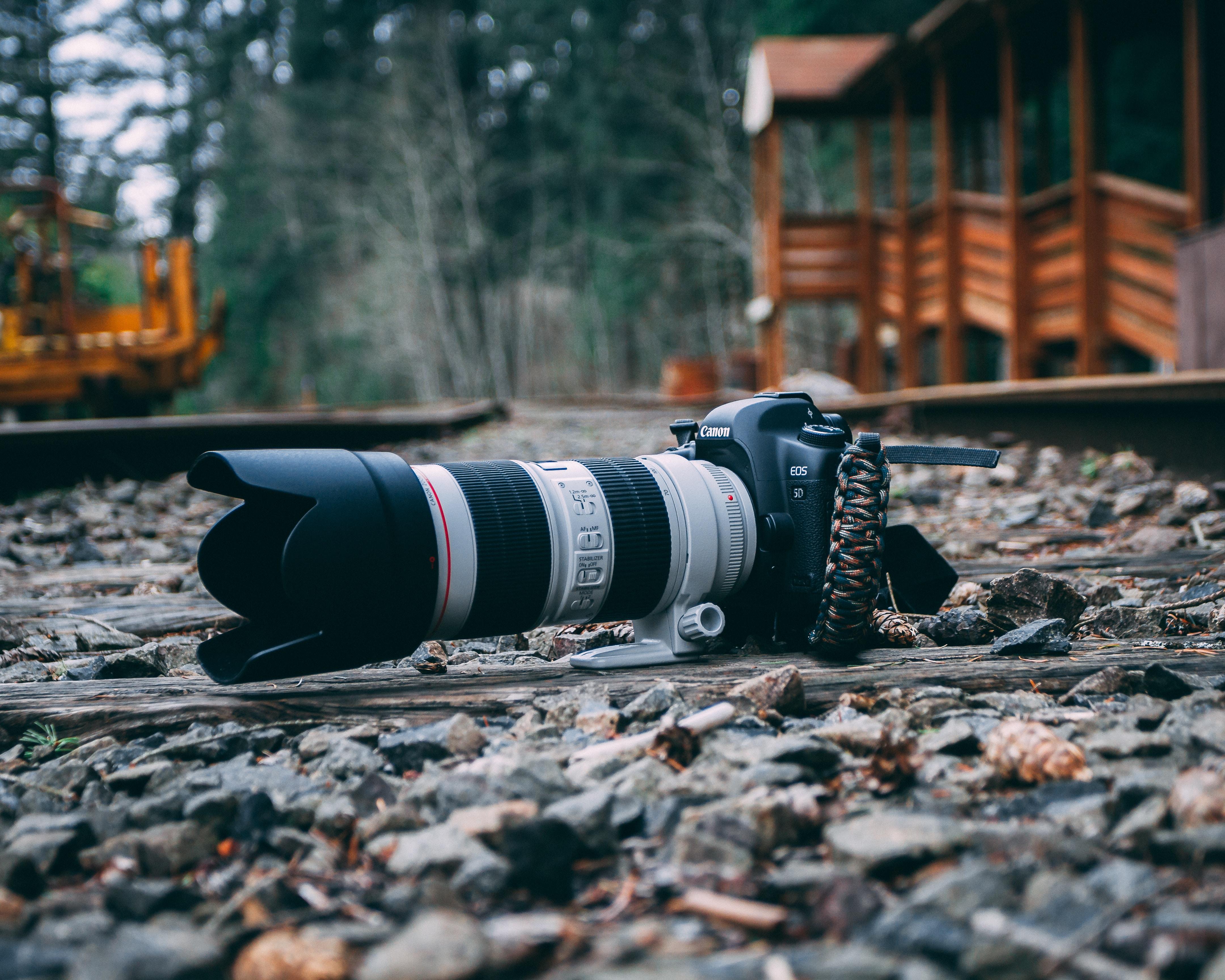 white and black DSLR camera on stone-filled ground near wooden establishment