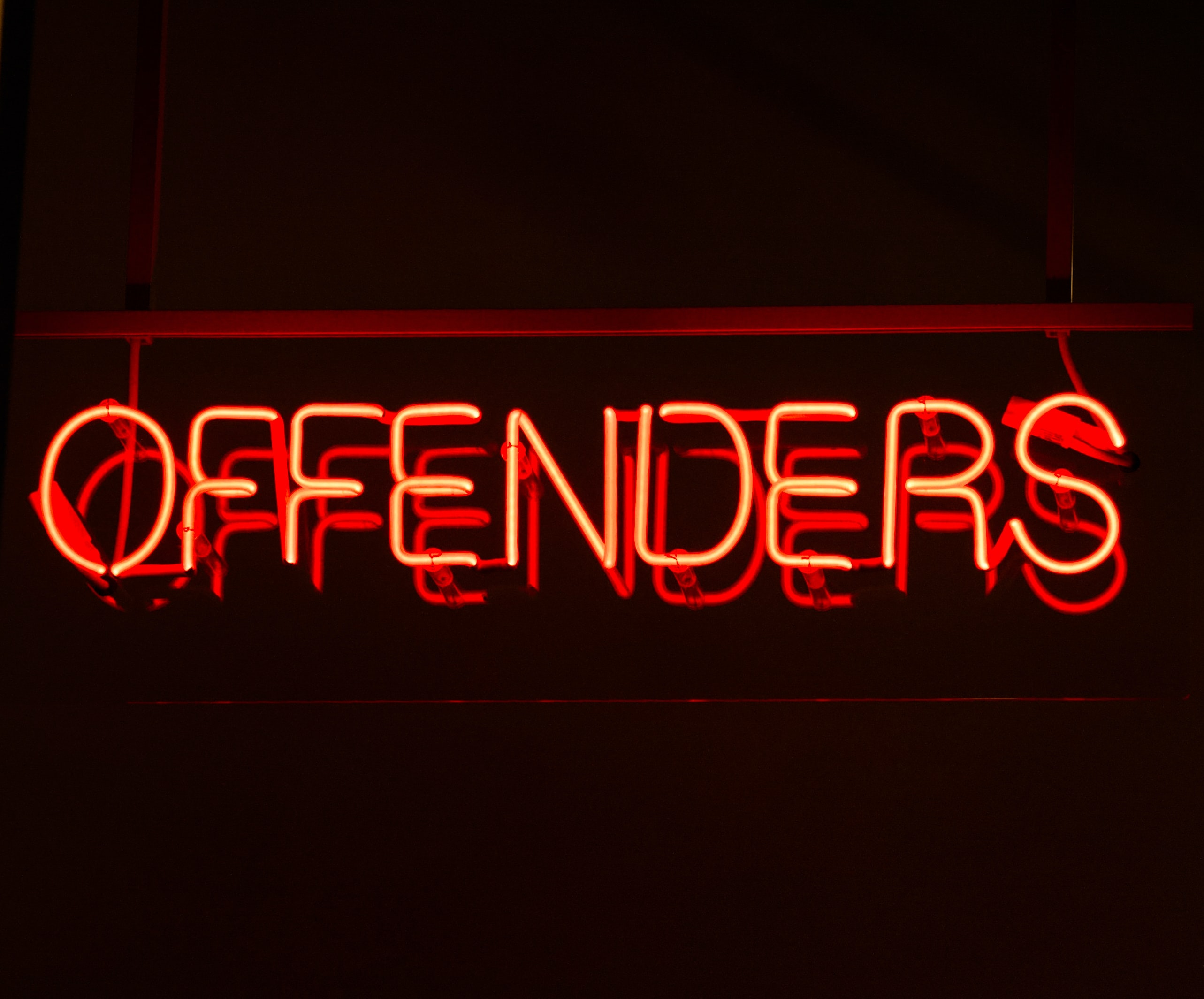 red neon lighted offenders signage