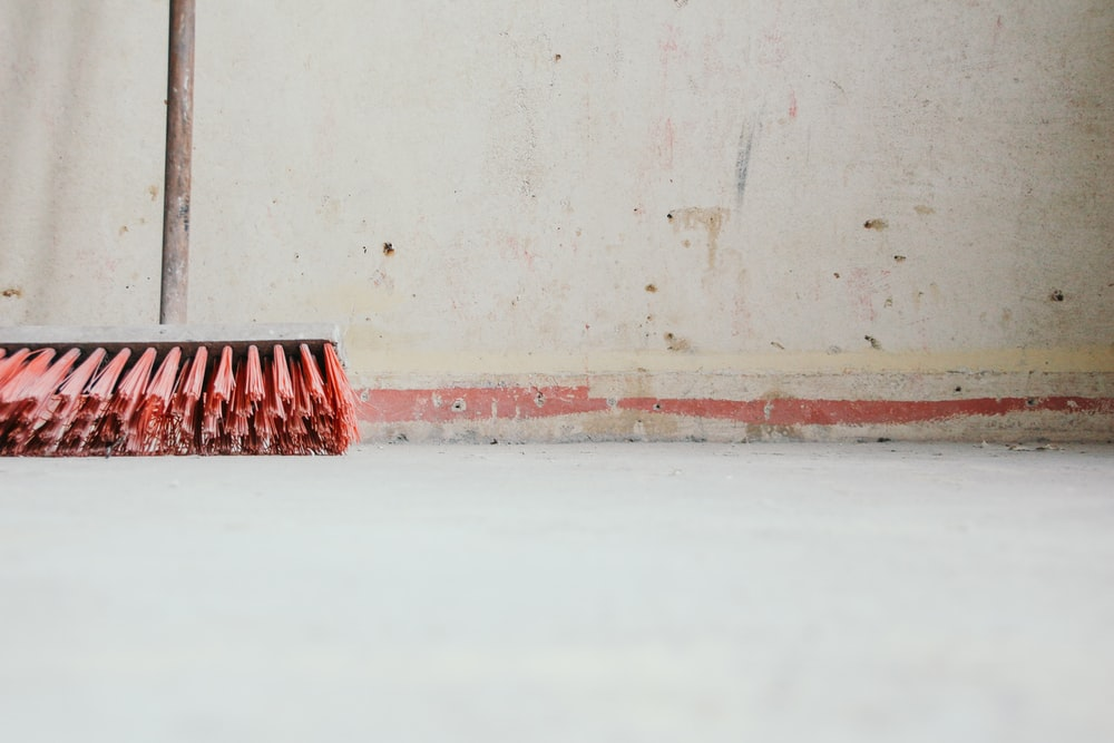 red push broom beside wall