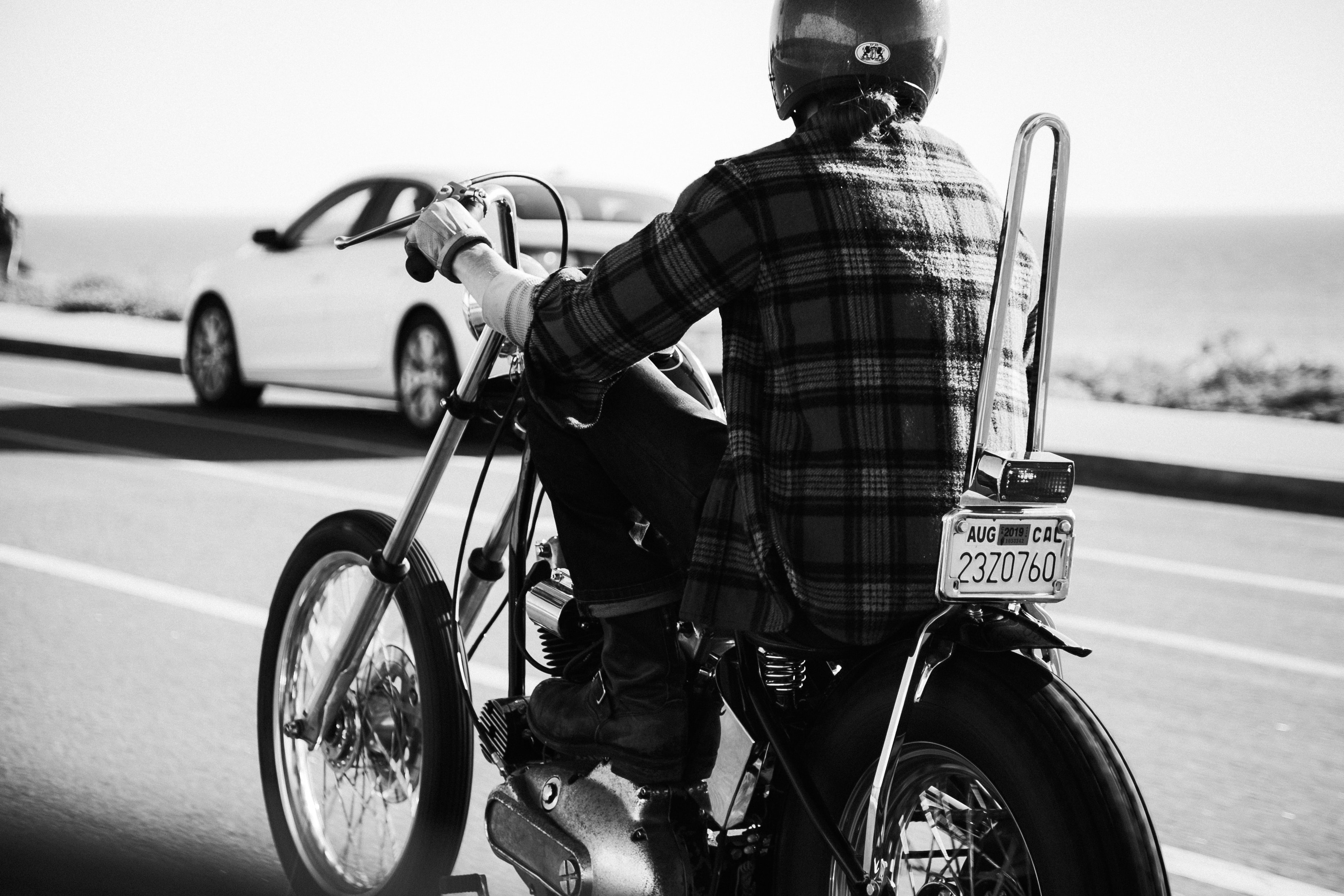 grayscale photo of person wearing plaid dress shirt riding chopper motorcycle