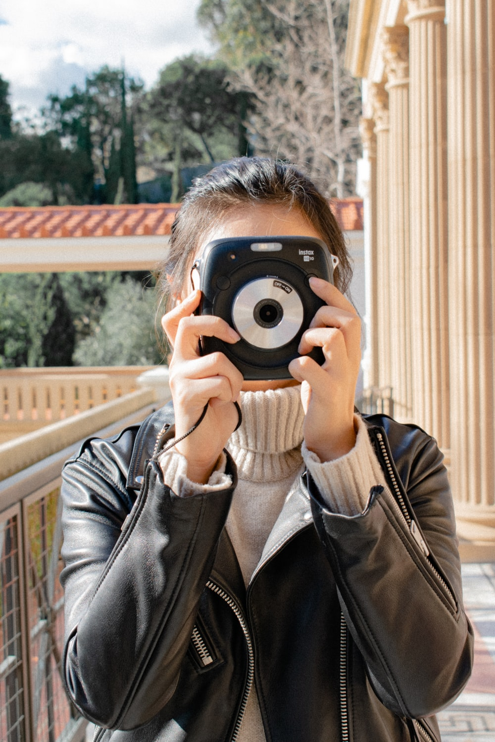 woman holding black instant camera