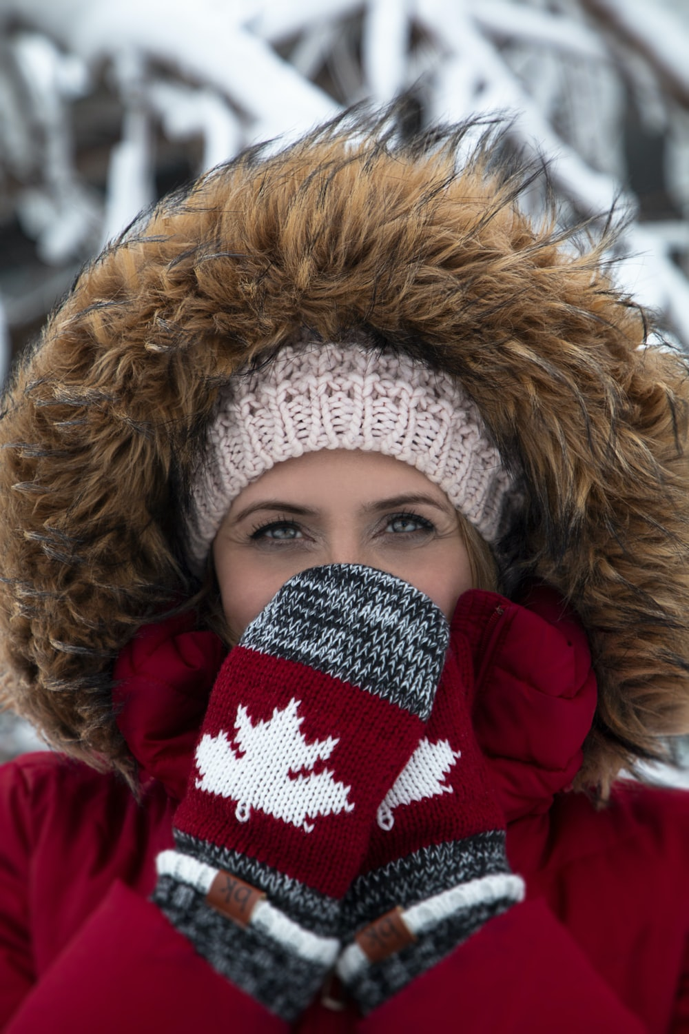 woman wearing red-and-brown parka coat and gray-and-red Canada knit mittens