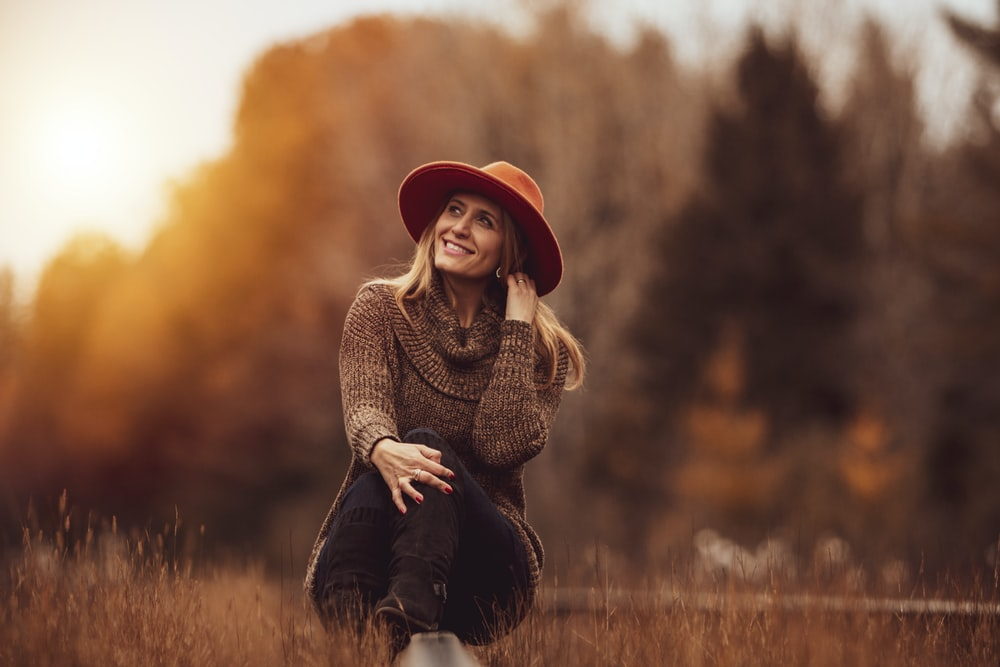 woman sitting on grass field and smiling
