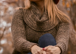 woman wearing brown sweater and orange hat