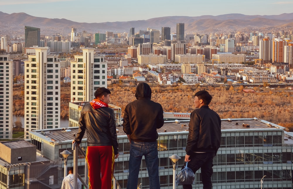 three man standing on top of building during daytime