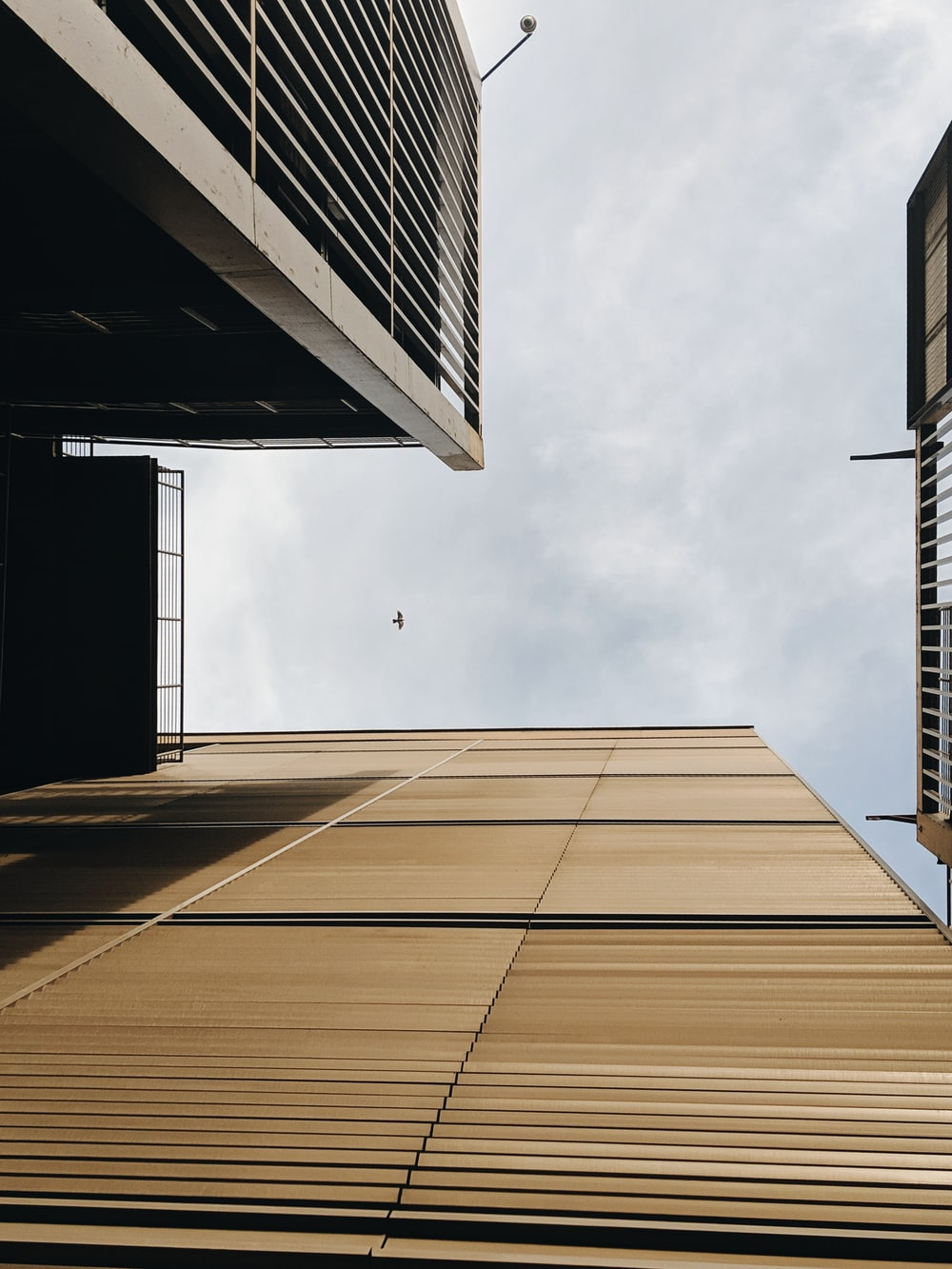 worm's-eye view photo of brown building across clouds