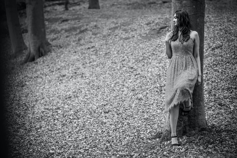 grayscale photography of woman wearing dress leaning on tree