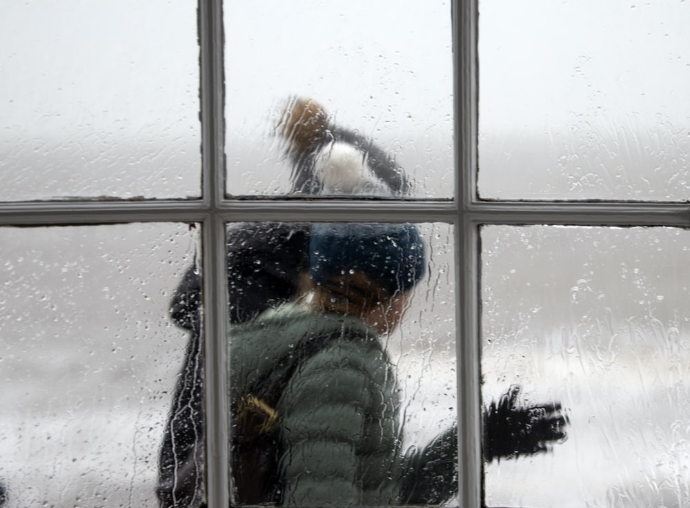 glass window across person wearing gray bubble jacket