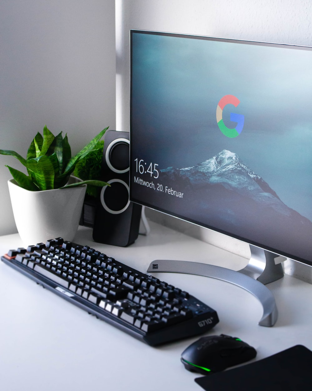 black Logitech G710+ wireless keyboard and wireless mouse near gray flat screen computer monitor on table