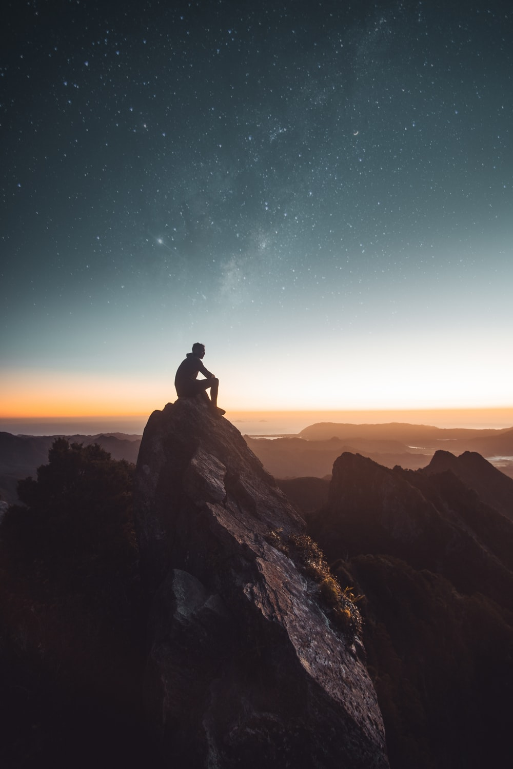 silhouette of person sitting on rock formation during golden hour