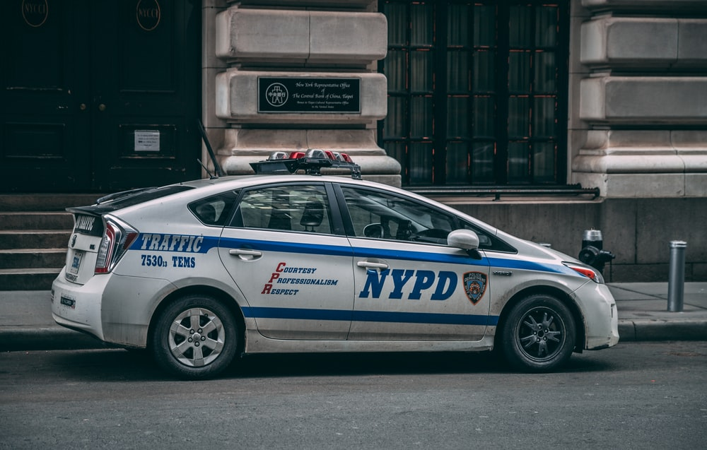 white Toyota Prius NYPD Cruiser parked near concrete building during daytime