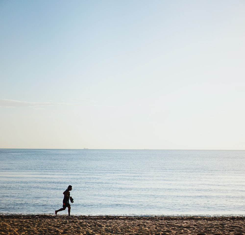person running on shore during daytime
