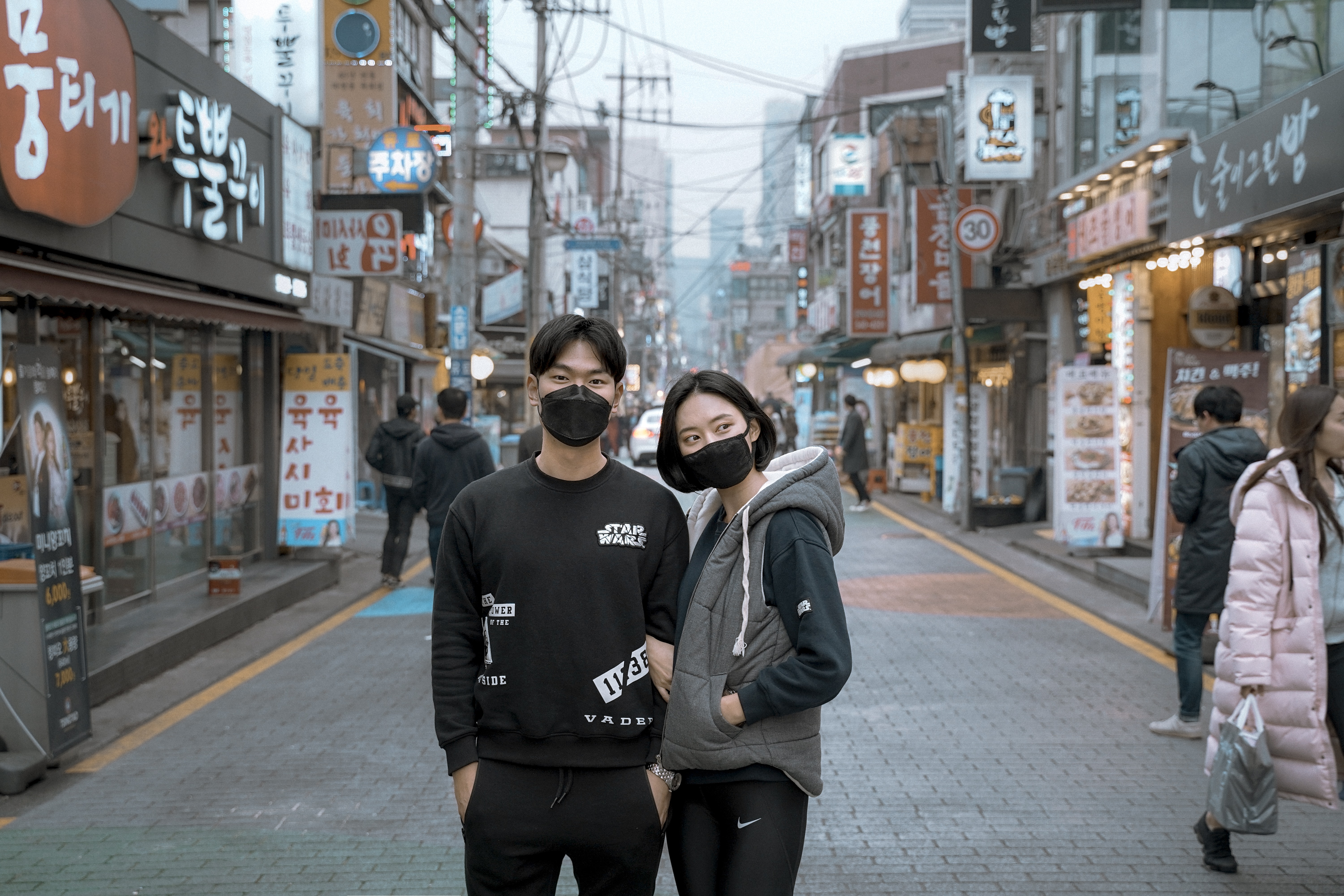 two man and woman wearing face mask in between building