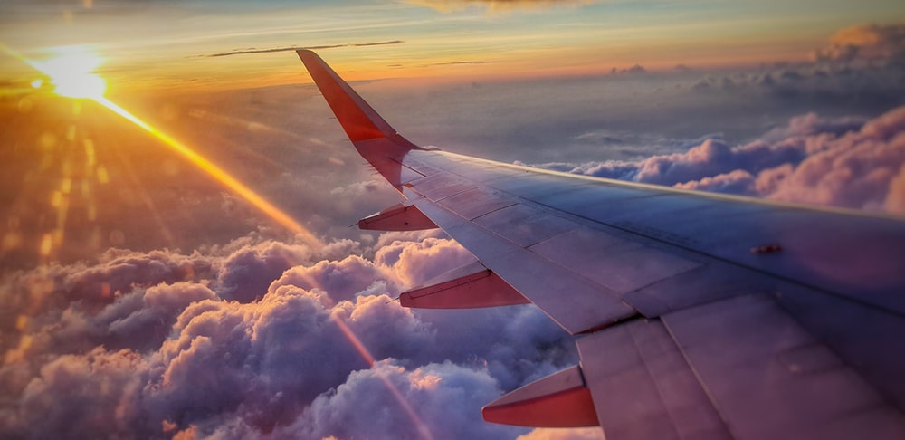 aerial photography of airplane flying over sea of clouds  alitalia voli giovani offerte