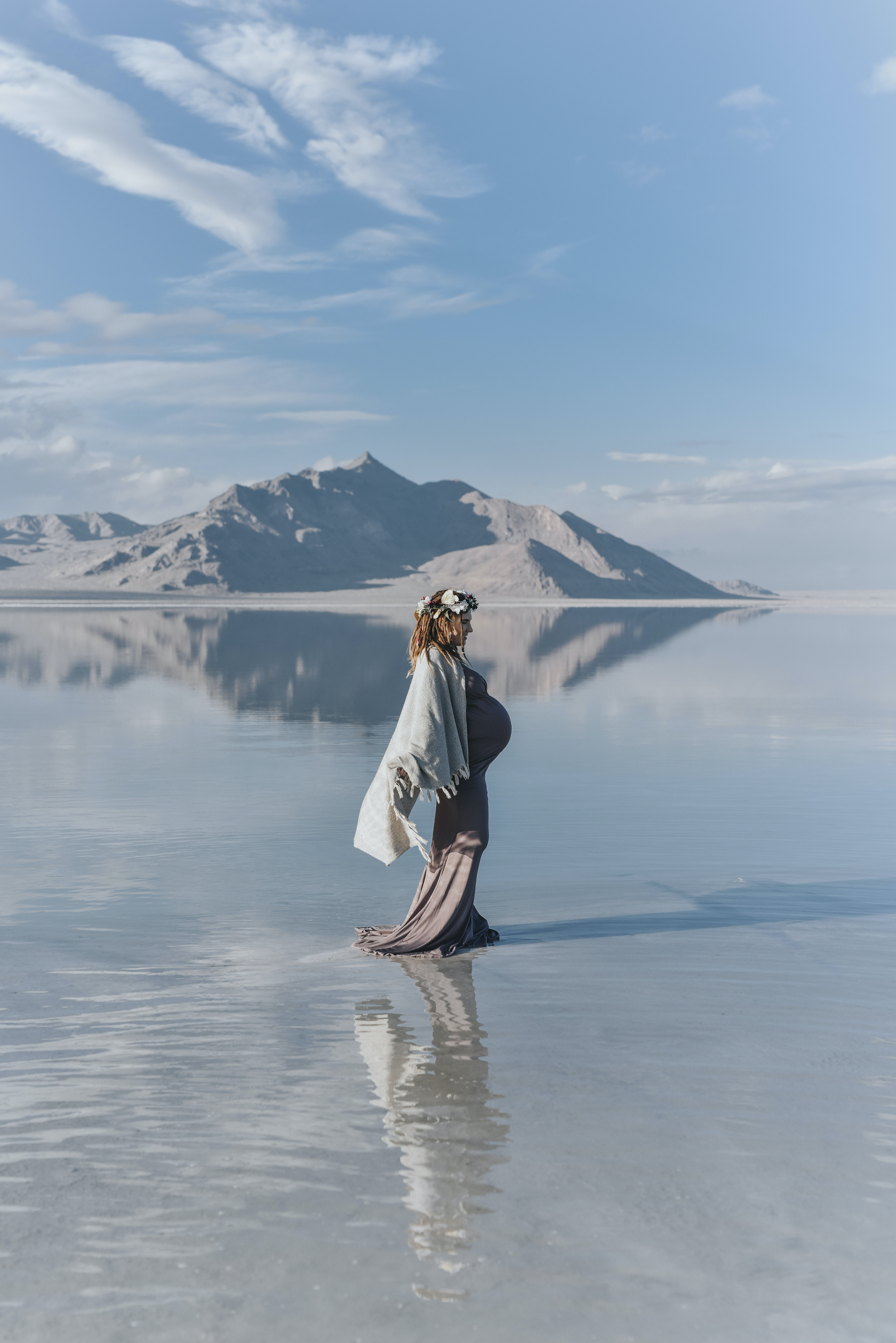 pregnant woman standing on body of water