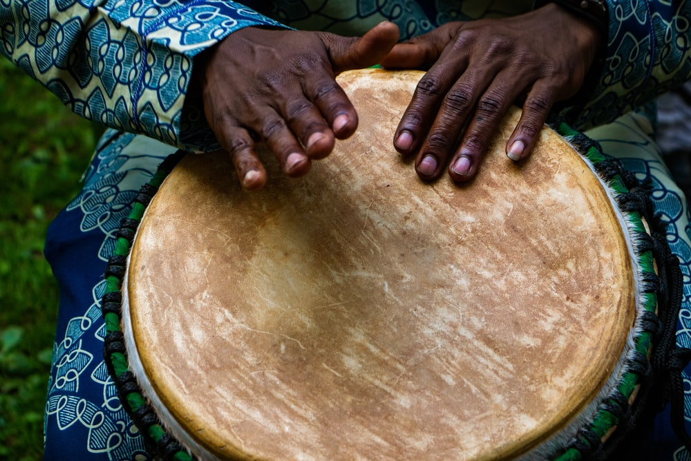 person tapping on traditional drum instrument