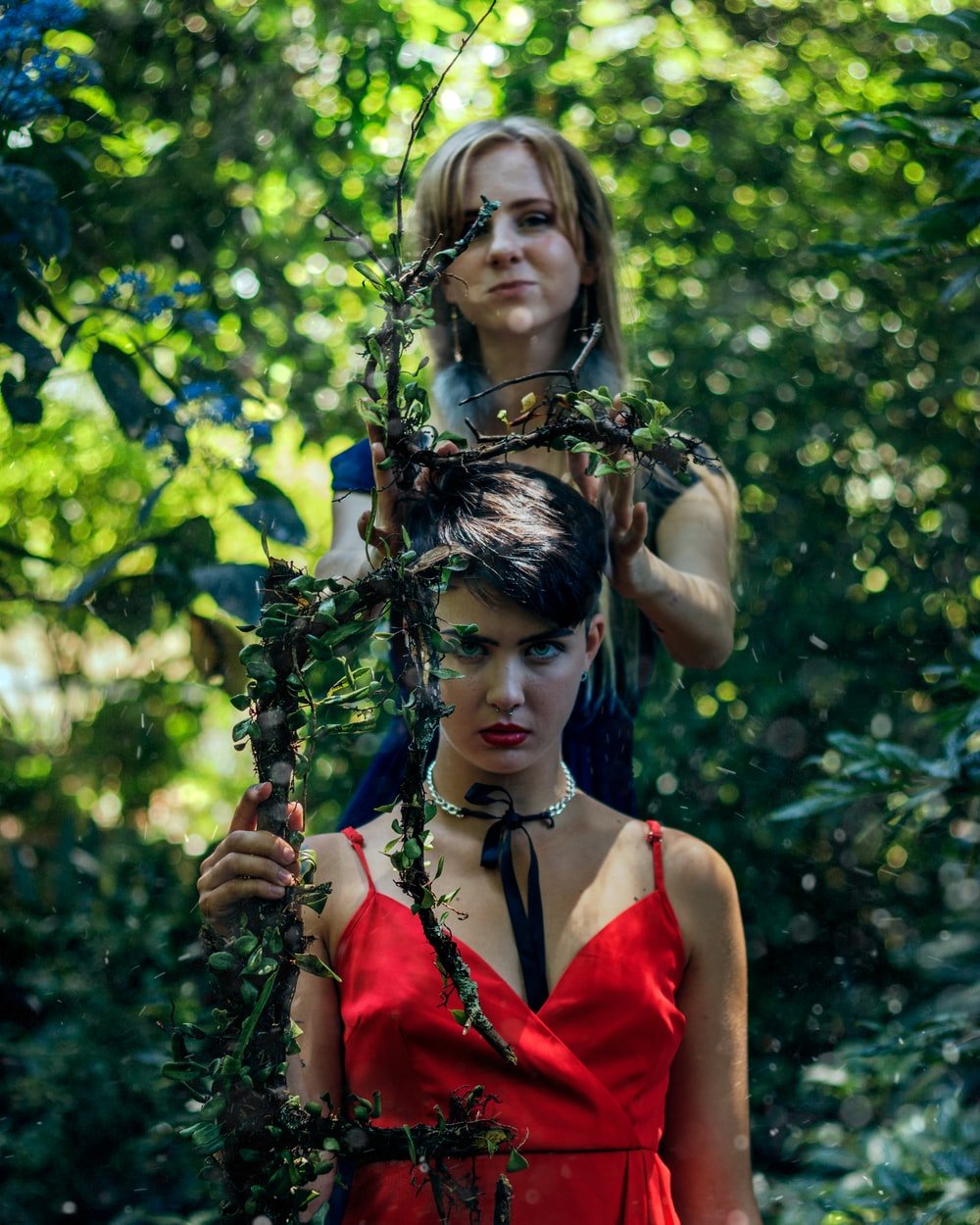 two woman holding twigs surrounded by trees during daytime