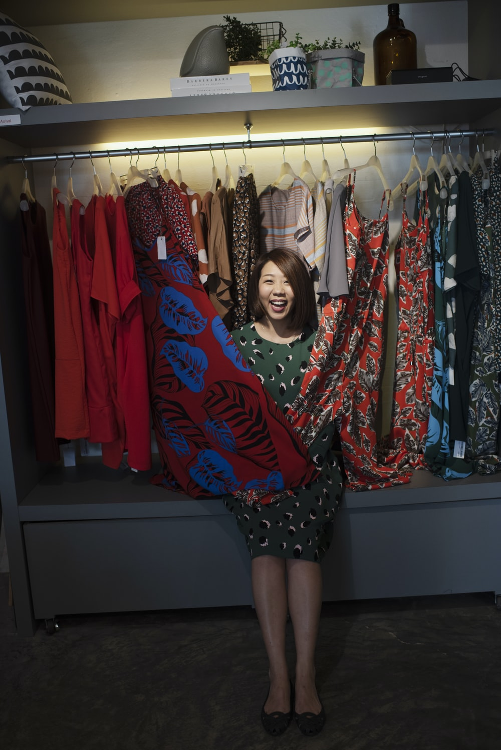 smiling woman standing on different dresses lot