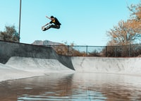 man doing tricks on skateboard in mid air on ramp pit with body of water