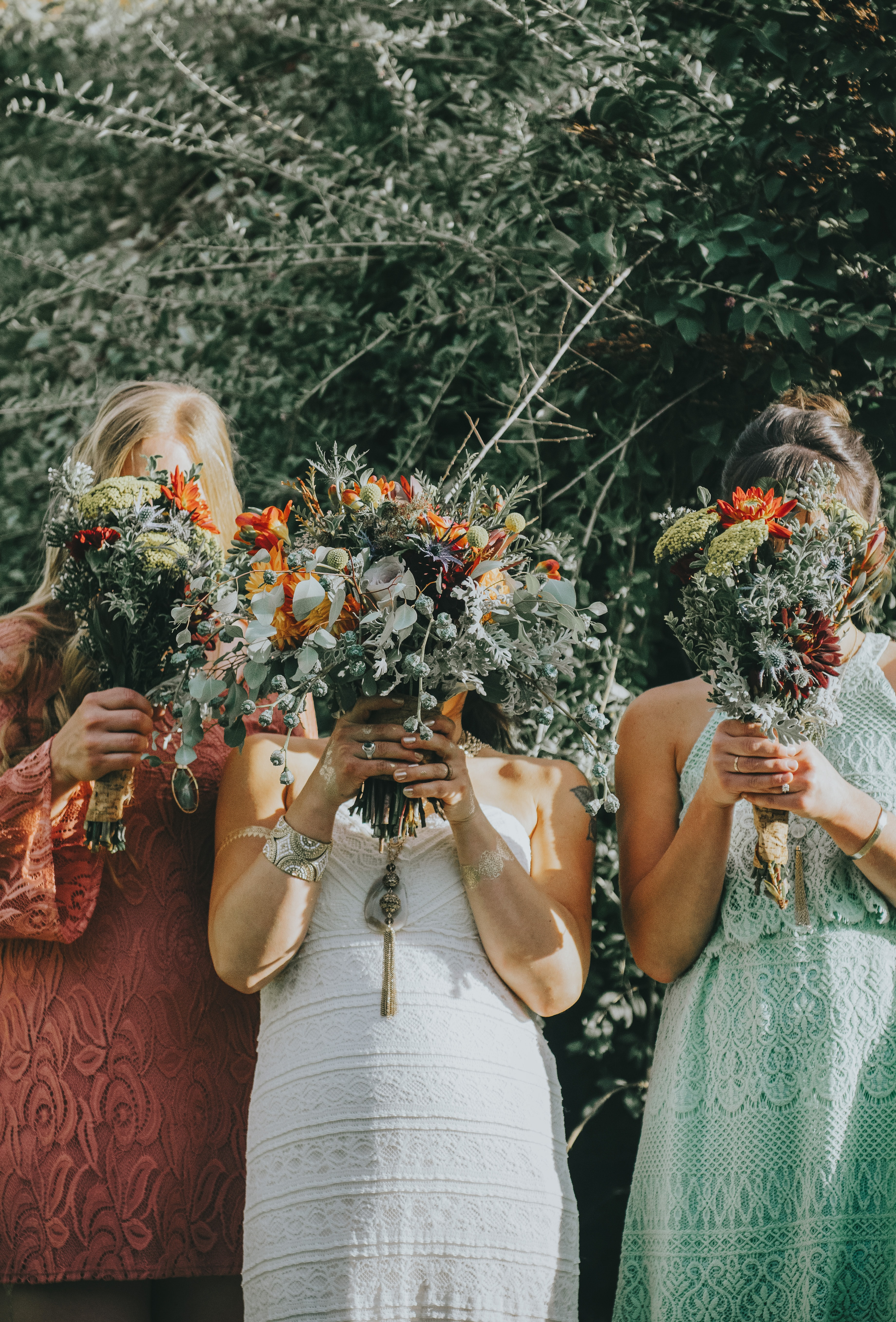 three women covering their faces with bouquet of flowers