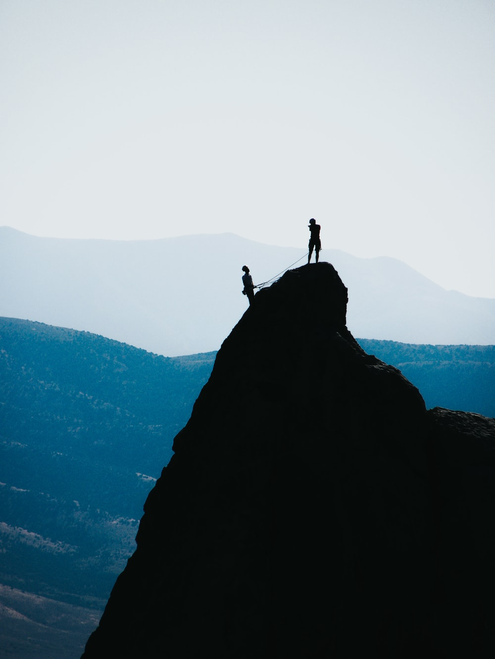 silhouette of two people standing on mountain during daytime