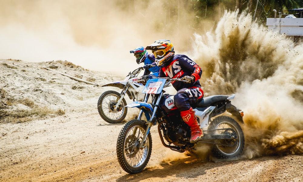two men riding motocross bikes on brown sand