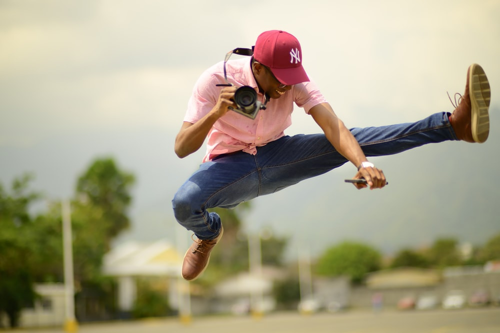 man jumping while holding camera