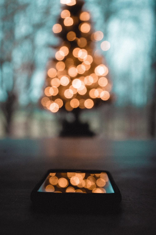 orange bokeh lights and black phone