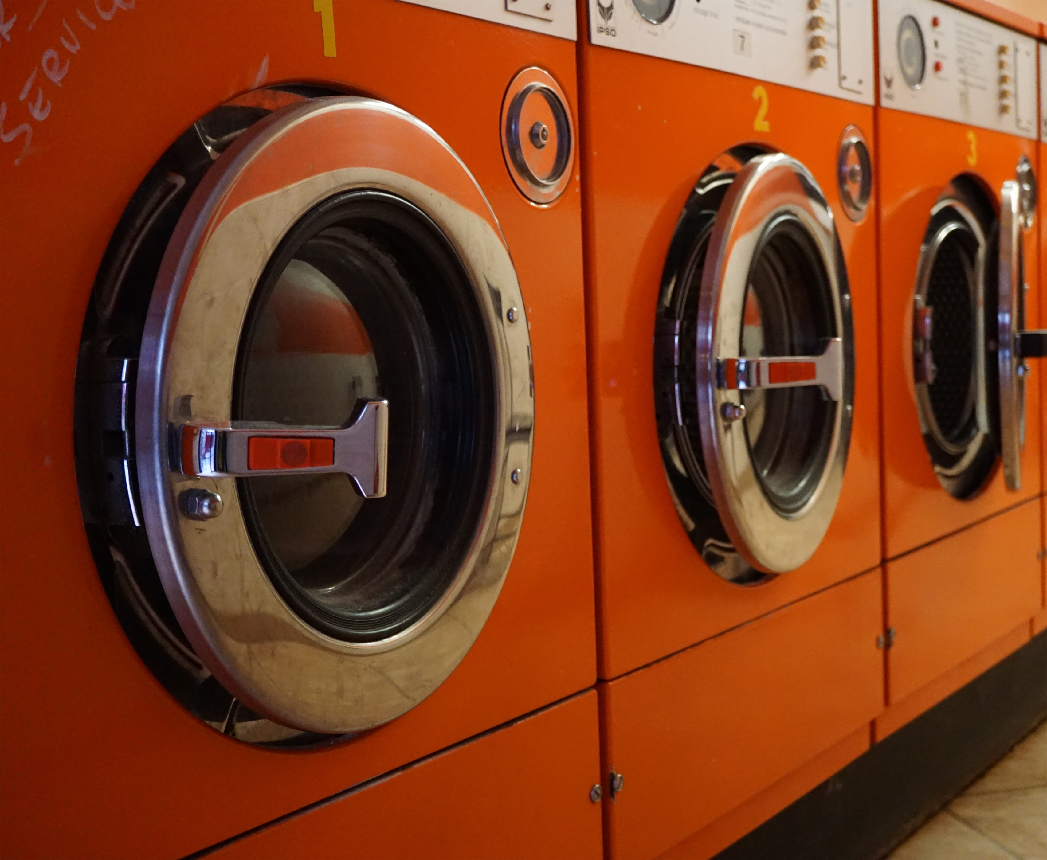 three red front-load clothes dryers
