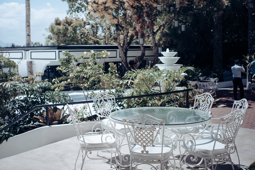 white cast-iron metal framed glass-top outdoor table set