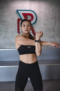woman in black Nike sports bra stretching arms