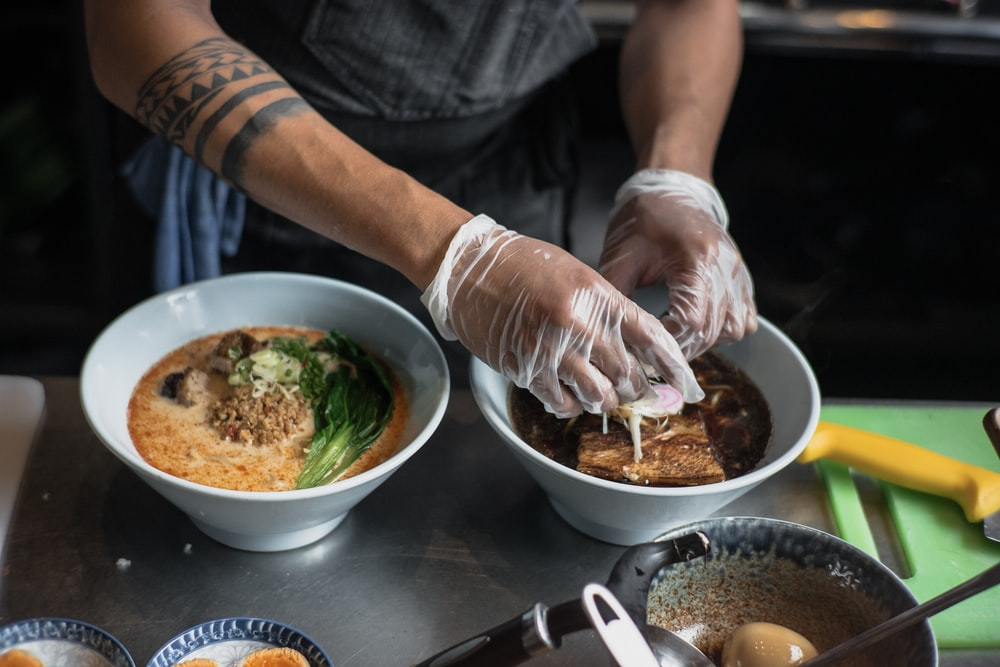 person using plastic gloves making food