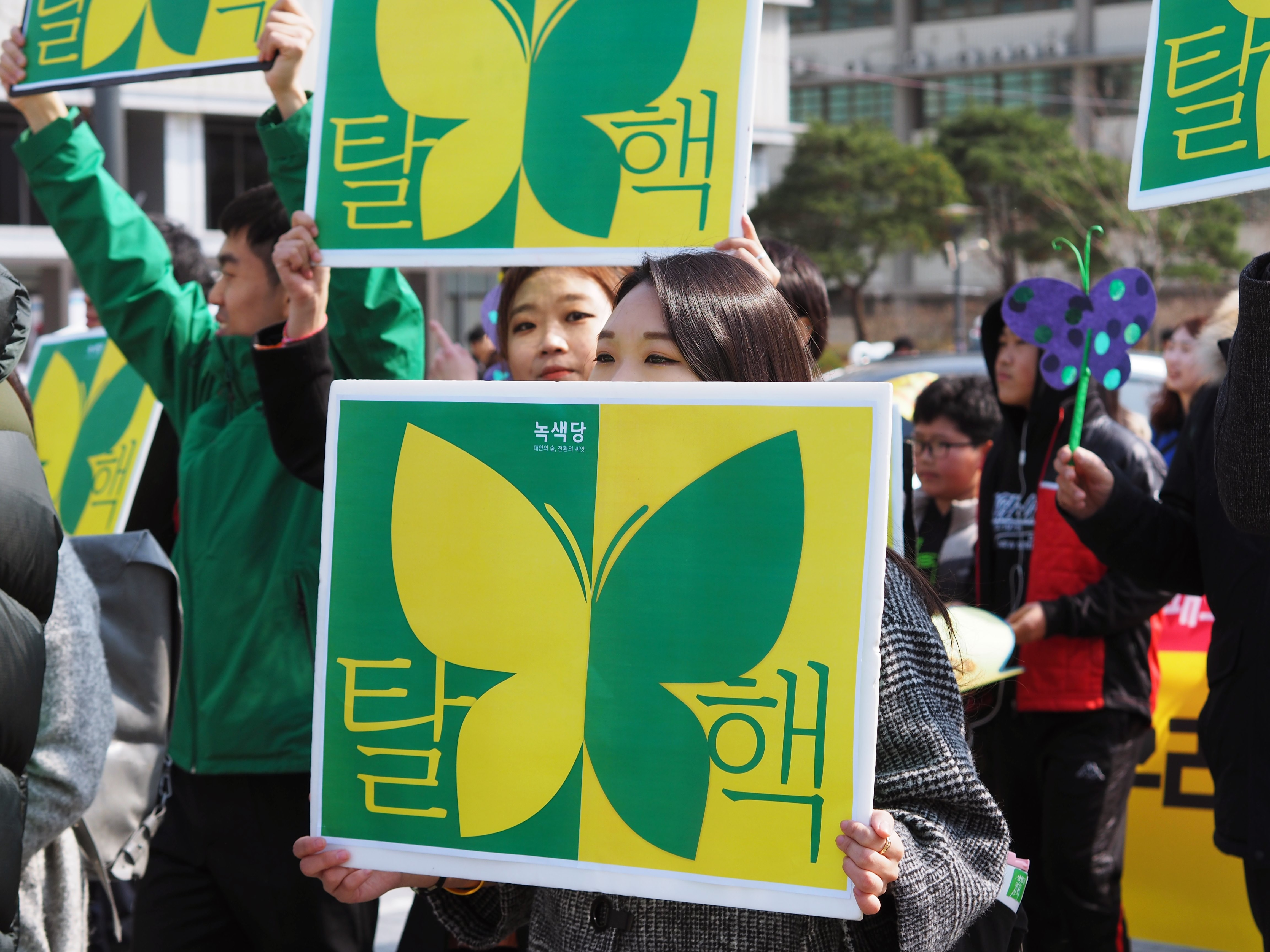 people holding butterfly signs