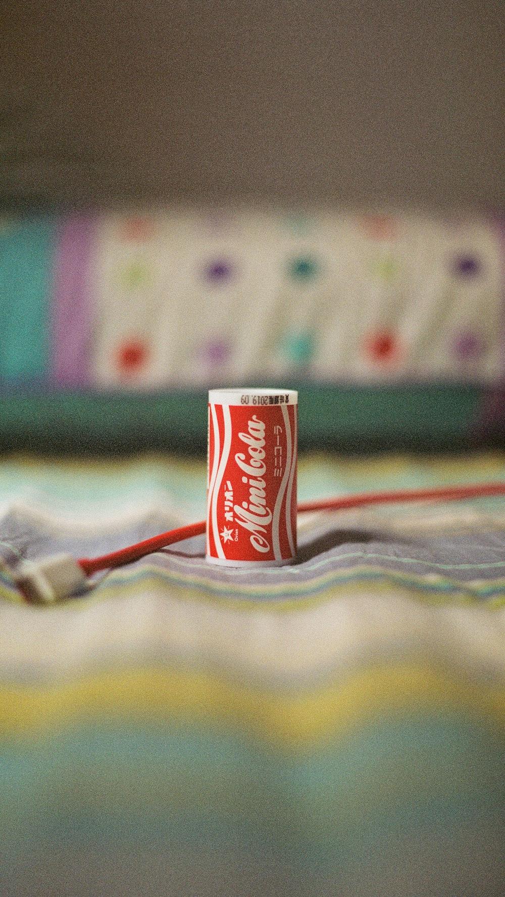 Mini Cola soda can on multicolored textile