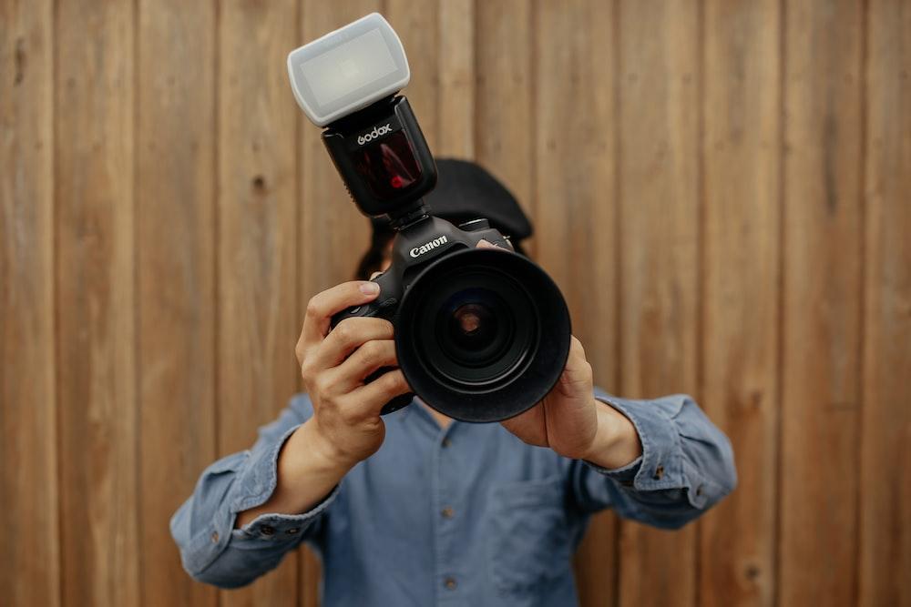 person holding black Canon camera