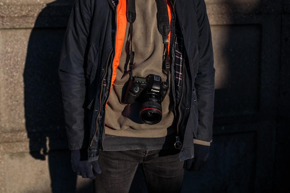 black DSLR camera on person's neck