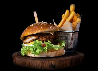 hamburger by french fries on board