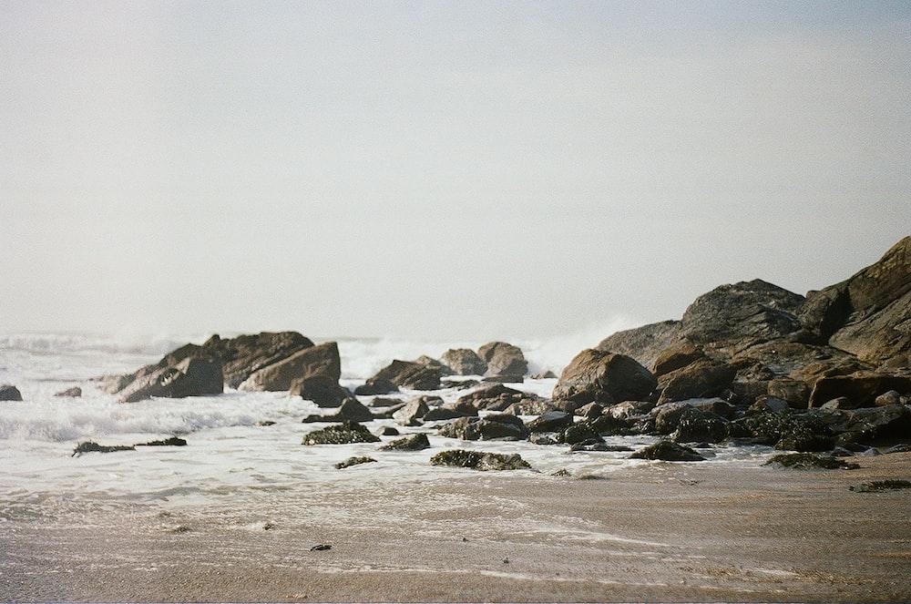 waves crashing on rocks at shore during daytime