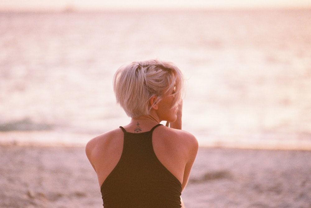 woman wearing black halter top facing beach
